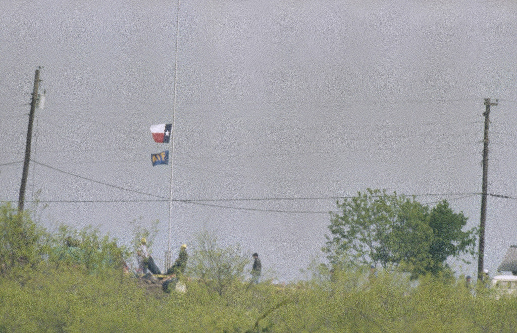 . Investigators carry a body bag past a flagpole with the Texas state flag and an ATF flag beneath it at half mast at the destroyed Branch Davidian compound near Waco, Texas on Thursday, April 23, 1993.  (AP Photo/Ron Heflin)