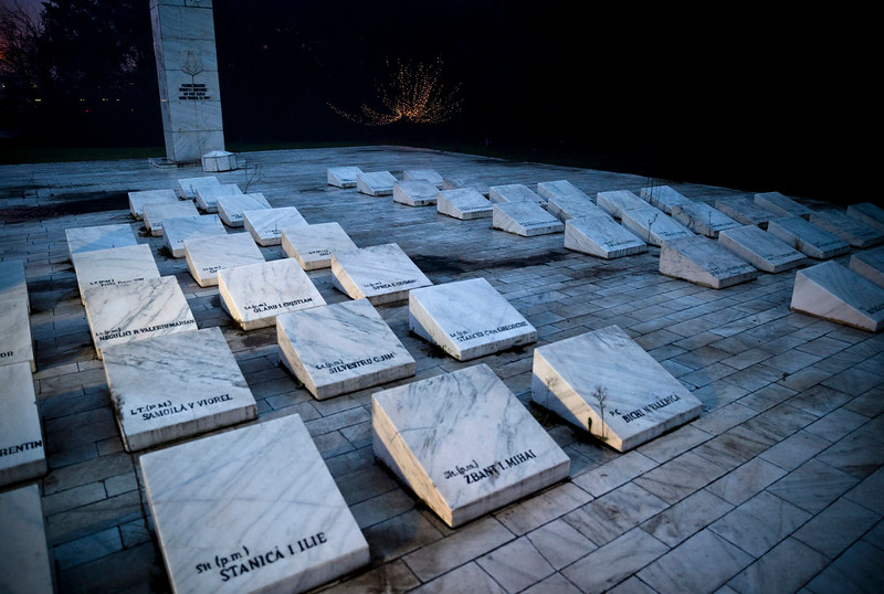 . A picture taken on Dec. 15, 2014 shows a monument by tombstones carrying names of Romanian military personnel killed in fighting around the Otopeni airport during the anticommunist uprising 25 years ago, outside Bucharest, Romania.  (AP Photo/Vadim Ghirda)
