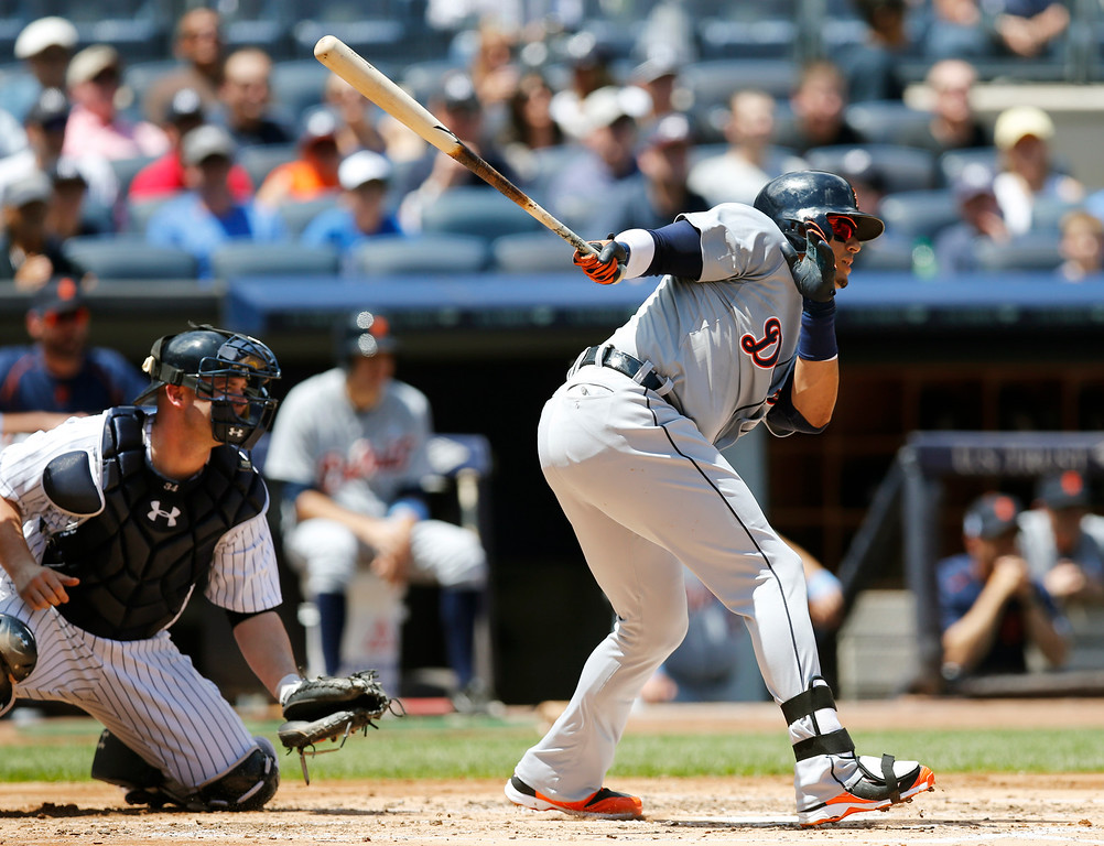 . Detroit Tigers designated hitter Victor Martinez, right, hits a second-inning two-run single in a baseball game against the New York Yankees at Yankee Stadium in New York, Sunday, June 21, 2015.  (AP Photo/Kathy Willens)