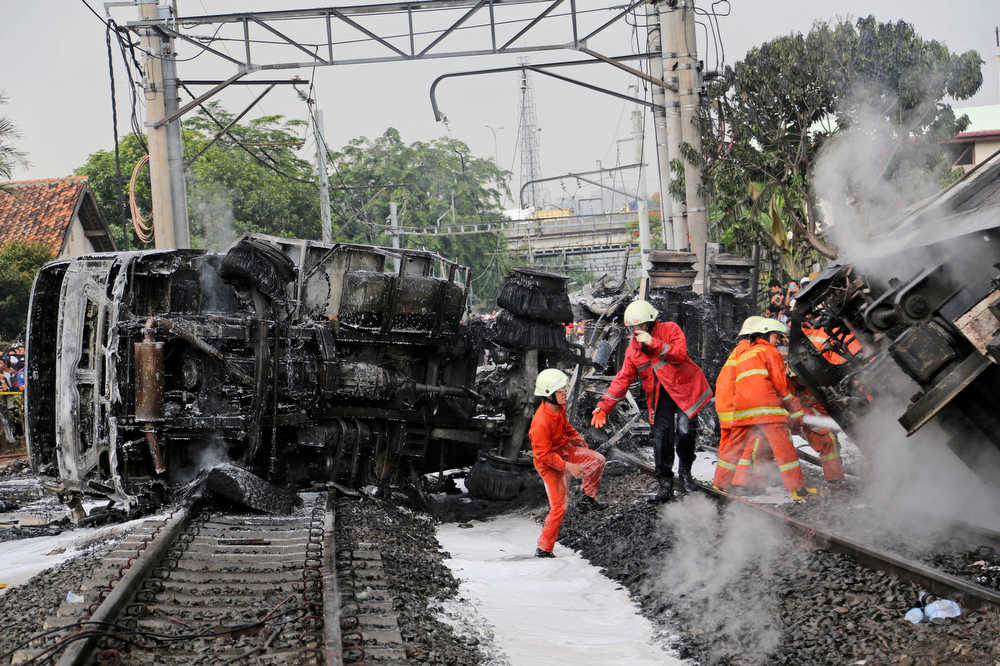 . Firefighters walk near the wreckage of a fuel tanker truck that was hit by a commuter train and caught fire on the outskirts Jakarta, Indonesia, Monday, Dec. 9, 2013. (AP Photo/Tatan Syuflana)