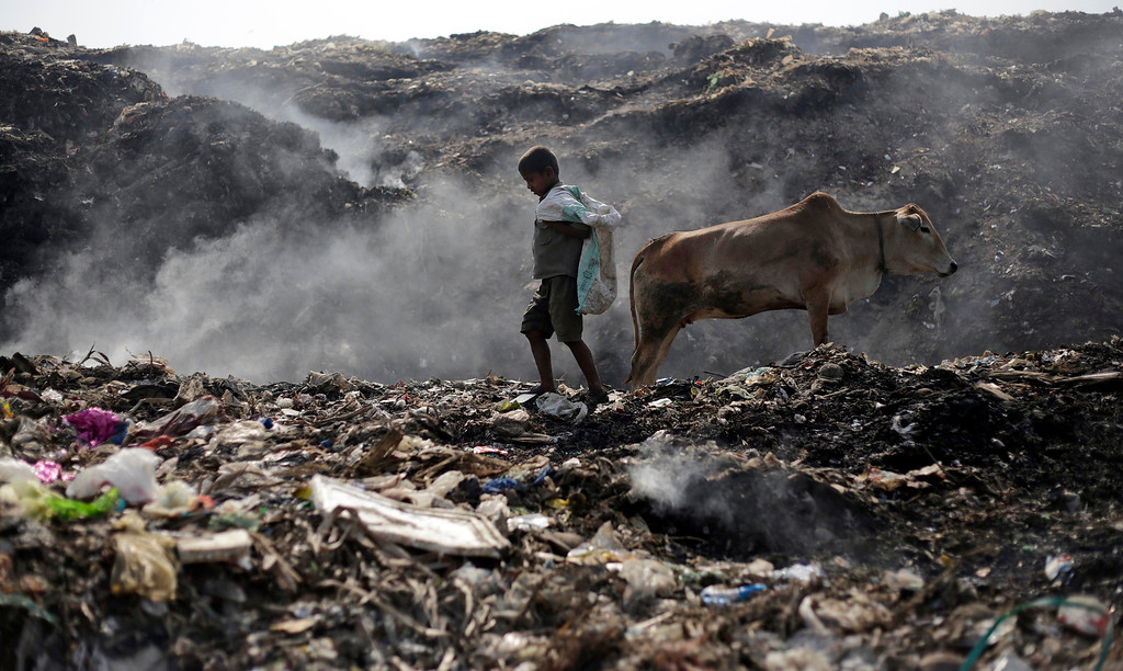 . A young ragpicker looks for recyclable items at a garbage dump on Earth Day, on the outskirts of Gauhati, India, Tuesday, April 22, 2014. People across the globe hold events to celebrate the Earth\'s environment and spread awareness on how to conserve its natural resources on Earth Day, observed annually on April 22. (AP Photo/Anupam Nath)