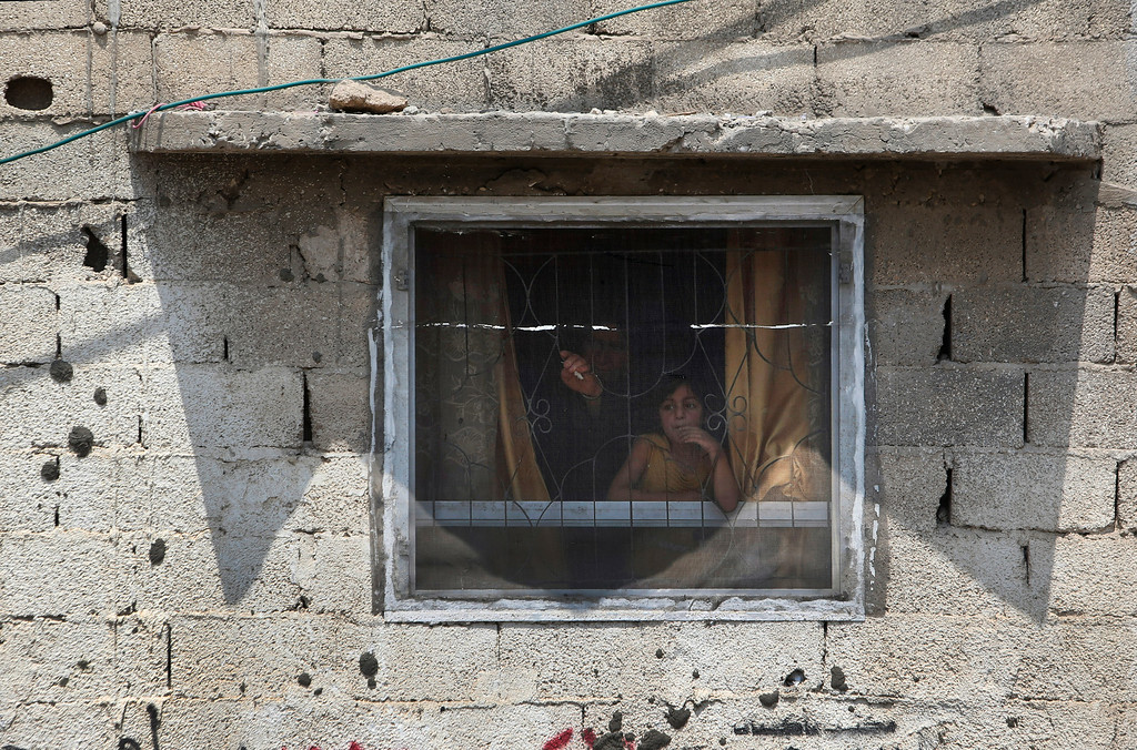 . Palestinians watch as mourners leave after the funeral of seven members of the Kelani family in Beit Lahiya, northern Gaza Strip, on Tuesday, July 22, 2014. Ibrahim Kelani, 53, his wife, Taghreed, and their five children were killed overnight in a strike on a Gaza City high-rise. Ibrahim\'s brother Saleh Kelani said Tuesday that his brother and his brother\'s children, ranging in age from 4 to 12, had German citizenship, but his wife did not. The family had rented the apartment in the high-rise after fleeing their home in the northern Gaza town of Beit Lahiya which came under heavy shelling by the Israeli army. (AP Photo/Majed Hamdan)