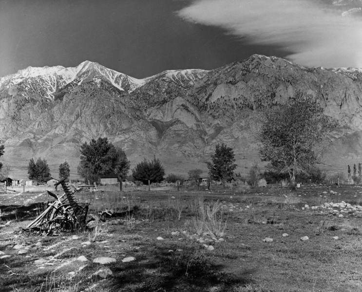 . View of the east slope of snow-capped Sierra Nevada Mountains near Bishop. Small homes are seen, and farm equipment lies at left in the foreground.   (Los Angeles Public Library)