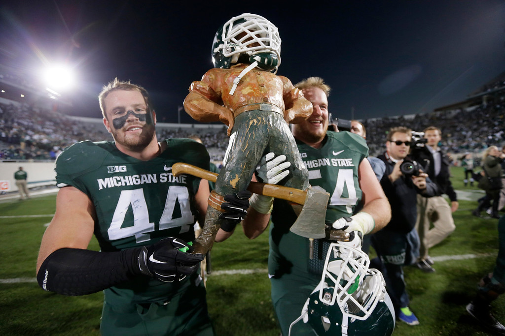 . Michigan State defensive end Marcus Rush (44) and guard Connor Kruse (54) carry off the Paul Bunyan trophy after their 35-11 win over in an NCAA college football game in East Lansing, Mich., Saturday, Oct. 25, 2014. (AP Photo/Carlos Osorio)