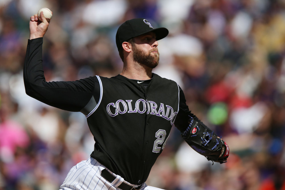 . Colorado Rockies starting pitcher Jordan Lyles works against the Cincinnati Reds in the third inning of a baseball game in Denver, Sunday, Aug. 17, 2014. (AP Photo/David Zalubowski)