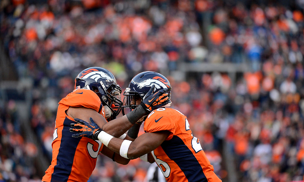 Description of . Denver Broncos free safety Rahim Moore (26) and Denver Broncos outside linebacker Wesley Woodyard (52) celebrate sacking Kansas City Chiefs quarterback Brady Quinn (9) during the second quarter. The Denver Broncos vs Kansas City Chiefs at Sports Authority Field Sunday December 30, 2012. Joe Amon, The Denver Post