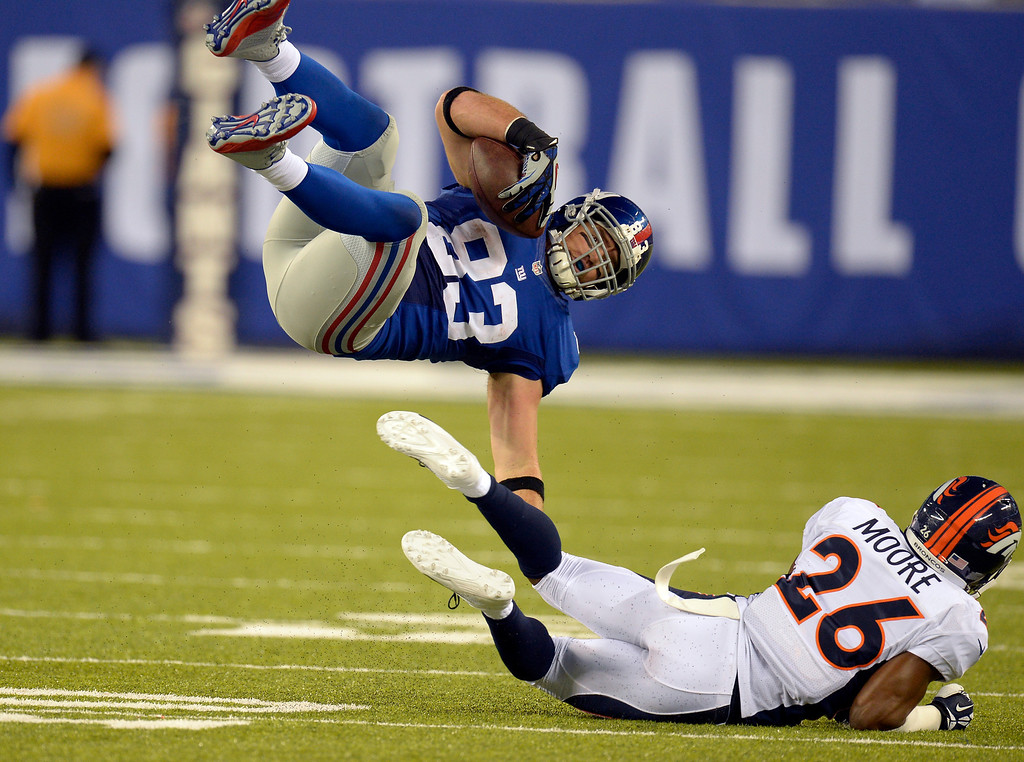 . EAST RUTHERFORD , NJ -SEPTEMBER 15: Denver Broncos free safety Rahim Moore (26) hits New York Giants tight end Brandon Myers (83) low to send him flying during the fourth quarter September 15, 2013 MetLife Stadium. (Photo by John Leyba/The Denver Post)