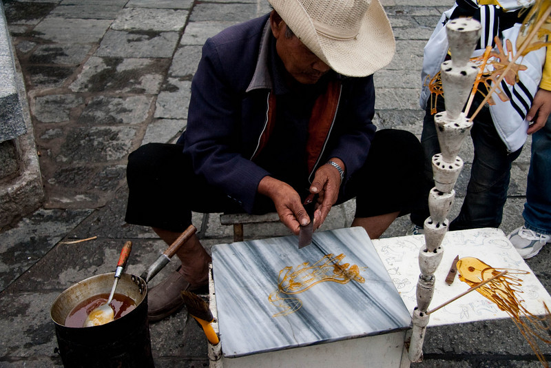 This street seller heats up the candy in a wok on top of a self-made stove, then uses a ladle to pour the shape of various animals onto the stone which is very cool.  The candy hardens up quickly then he uses a knife to lift up the candy and also presses down the skewer.