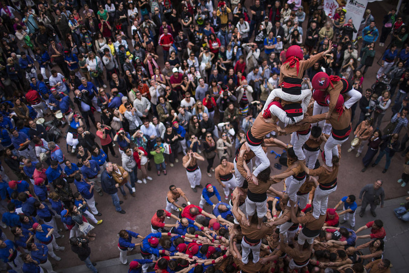 """. Members of a Castellers form their famous human tower called \""""castell\"""", as one of its members mounts the top, waving to the crowd in the Barcelona neighborhood of Gracia, Catalonia, Spain on Sunday May 19 2013. A \""""castell\"""" is a human tower traditionally built during festivals in many places in Catalonia. At these festivals, several \""""colles\"""" or teams, compete to build the most impressive towers they can. (AP Photo/Emilio Morenatti)"""
