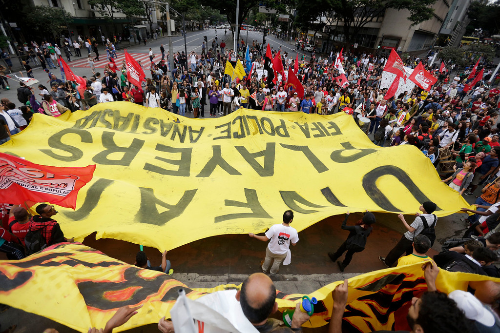 ". Demonstrators hold a banner that reads ""Unfair players, FIFA police\"" in Belo Horizonte, Brazil, Thursday, June, 12, 2014. Demonstrators gathered in downtown Belo Horizonte to protest against the 2014 World Cup soccer tournament. (AP Photo/Bruno Magalhaes)"