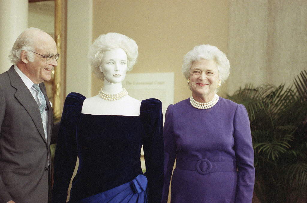 . First lady Barbara Bush presents her inaugural gown to the Smithsonian Institution in Washington on Tuesday, Jan. 9, 1989, where it will be displayed along with the collection of the gowns from previous first ladies. Man at left is unidentified. (AP Photo/Bob Daugherty)