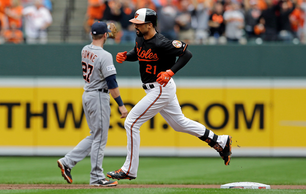. Baltimore Orioles\' Nick Markakis, front, rounds the bases past Detroit Tigers shortstop Andrew Romine after hitting a two-run home run in the third inning of Game 2 in baseball\'s AL Division Series in Baltimore, Friday, Oct. 3, 2014. (AP Photo/Patrick Semansky)