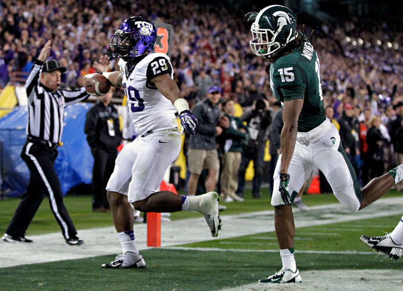 . TCU running back Matthew Tucker (29) scores a touchdown as Michigan State cornerback Trae Waynes (15) defends during the first half of the Buffalo Wild Wings Bowl NCAA college football game, Saturday, Dec. 29, 2012, in Tempe, Ariz. (AP Photo/Matt York)