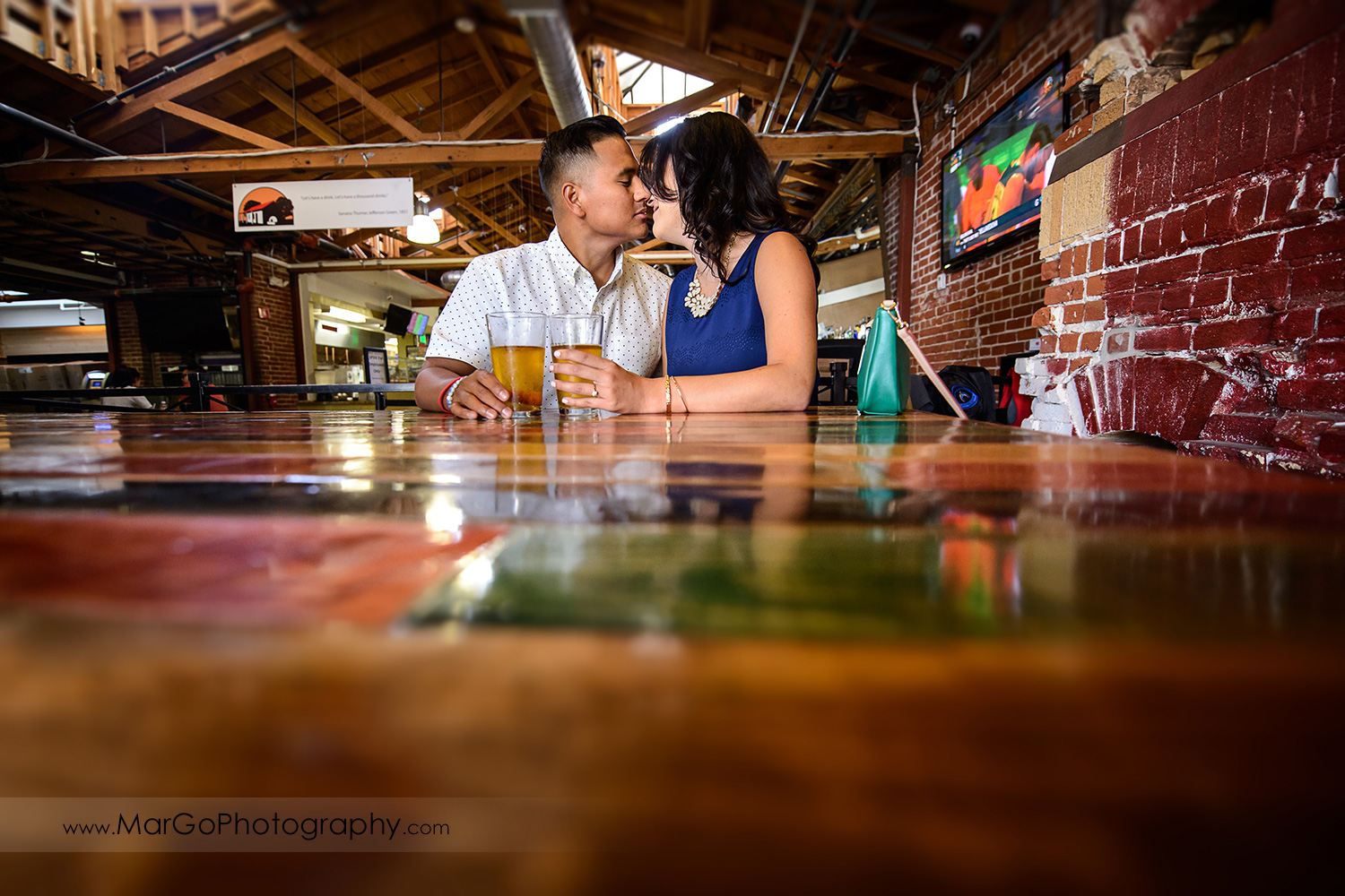 woman in blue dress and man in white shirt kissing and drinking beer during engagement session at San Pedro Square Market in San Jose