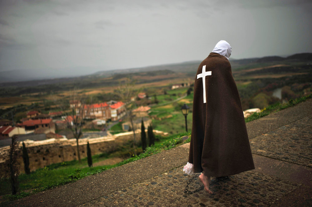 . A masked penitent from La Santa Vera Cruz brotherhood walks along the way taking part in an Easter procession known as \'Los Picaos\' in the small village of San Vicente de la Sonsierra, northern Spain on Friday, March 29, 2013. Penitents, or disciplinants, take part on the procession lashing themselves  as an act of faith and penance, a tradition dating from the early 16th century. (AP Photo/Alvaro Barrientos)
