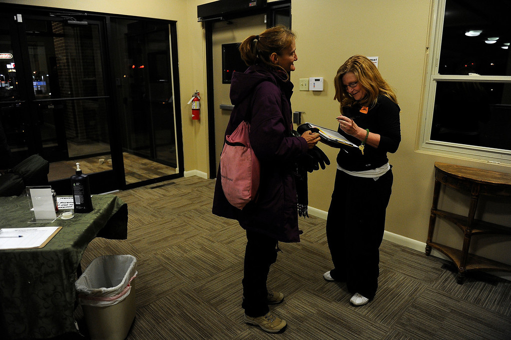 . GOLDEN, CO - JANUARY 22: Tracy Thayer, right, checks in Sherry White as she takes emergency overnight shelter at Applewood Community Church in Golden, Colorado on January 22, 2014. The Jefferson County Action Center began partnering with churches last year to offer emergency shelter for the homeless on severe weather nights. (Photo by Seth McConnell/The Denver Post)