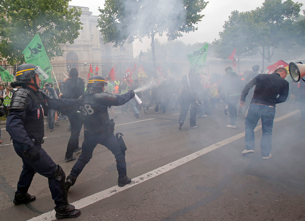 Description of . French riot police fire tear gas at striking train workers during a protest over a bill to reform the state-run railway system in Paris, Tuesday, June 17, 2014. A weeklong strike by rail workers has caused one of the worst disruptions to the country's rail network in years and is heating up as the reform bill goes to the lower house of Parliament for debate Tuesday. France's Foreign ministry is in the background. (AP Photo/Michel Euler)