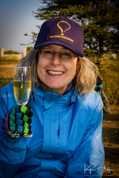 Mary enjoys the traditional glass of champagne after our hot air balloon has landed.