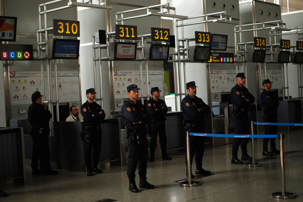 Description of . Spanish riot police officers stand guard at a British Airways check-in counter as Iberian workers (not pictured) protest in front of them during a strike at Pablo Ruiz Picasso Airport in Malaga, southern Spain February 18, 2013. Workers at loss-making Spanish flag carrier Iberia began a five-day strike at midnight on Monday, grounding over 1,000 flights and costing the airline and struggling national economy millions of euros. REUTERS/Jon Nazca