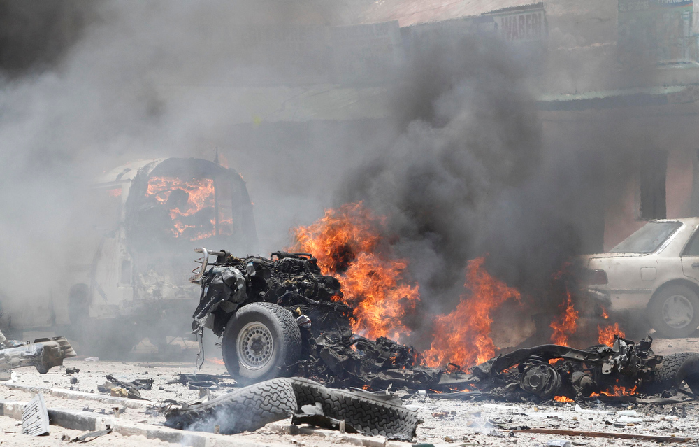 . Vehicles burn at the scene of an explosion near the presidential palace in Mogadishu March 18, 2013. A car bomb exploded near the presidential palace in Mogadishu on Monday, killing at least 10 people in a blast that appeared to target senior government officials, police said. REUTERS/Feisal Omar
