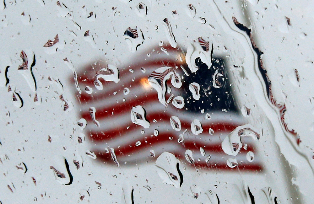 . An American flag flies at half staff in honor of those killed in the December 14 shootings at the Sandy Hook elementary school is reflected in raindrops on the window of a car in the center of Newtown, Connecticut December 21, 2012. A moment of silence was observed in Newtown Friday and across the U.S. followed by the ringing of church bells for each of the victims of the shootings. REUTERS/Mike Segar