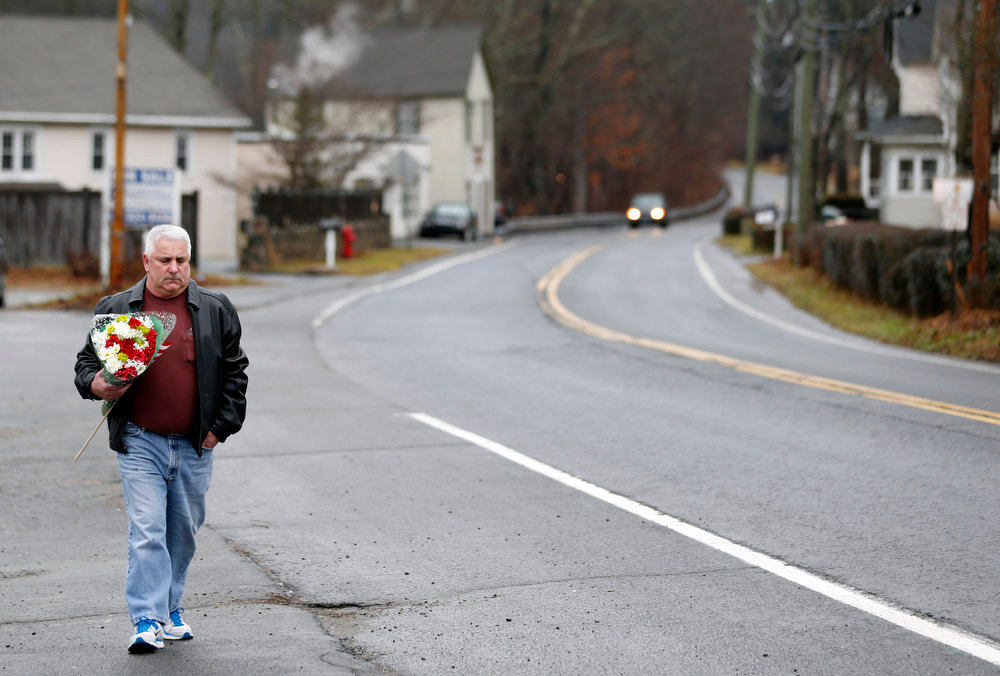 . A man walks with flowers in the Sandy Hook village of Newtown, Conn., as the town mourns victims killed in a school shooting, Monday, Dec. 17, 2012. Authorities say a gunman killed his mother at their home and then opened fire inside the Sandy Hook Elementary School in Newtown, killing 26 people, including 20 children, before taking his own life, on Friday. (AP Photo/Julio Cortez)