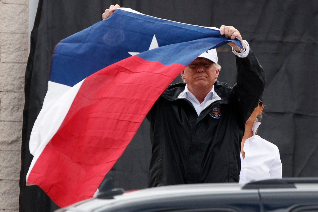 . President Donald Trump holds up a Texas flag after speaking with supporters outside Firehouse 5  in Corpus Christi, Texas, Tuesday, Aug. 29, 2017, where he received a briefing on Harvey relief efforts. (AP Photo/Evan Vucci)