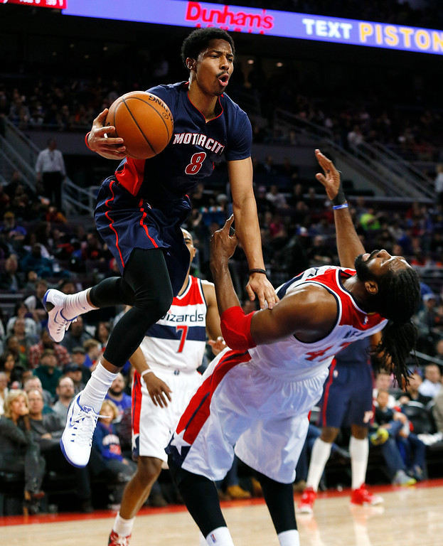 . Detroit Pistons guard Spencer Dinwiddie (8) drives against Washington Wizards guard John Wall (2) in the first half of an NBA basketball game in Auburn Hills, Mich., Sunday, Feb. 22, 2015. (AP Photo/Paul Sancya)