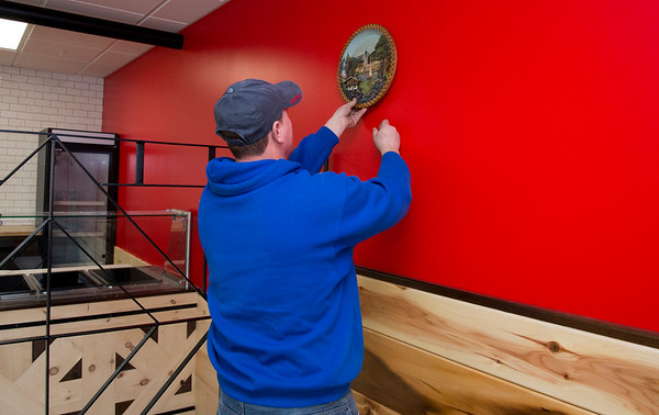11/04/19 Wesley Bunnell | StaffrrCo-owner of the Polish Plate at 1095 West St in Southington Radoslaw Kopacz looks for a spot on the wall to authentic wooden Polish plates he brought from Poland. Also shown are pieces of wood work he custom built for the restaurant drawing from his background in construction.