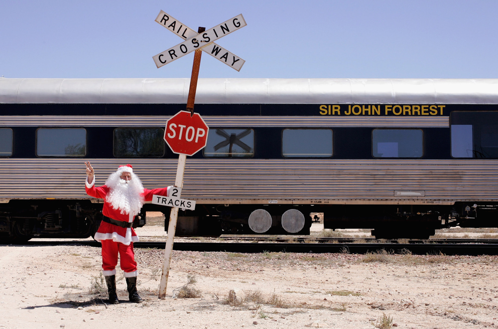 Description of . Santa Claus poses with the Indian Pacific  on December 4, 2009 in Cook, Australia. The Great Southern Railway's Indian Pacific travels the 4,352km between Sydney and Perth twice a week, crossing three states and includes the world's longest stretch of straight railway track on the Nullarbor Plain. Now in its ninth year, the Indian Pacific Outback Christmas Journey takes 65 hours to reach its destination while travelling through the Australian Outback to support remote regional communities as well as the Australian Royal Flying Doctor Service.  (Photo by Ashlee Ralla/Getty Images)