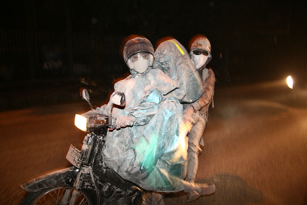 . Residents evacuate to a safe place by riding a motorbike in Malang, East Java province, on February 14, 2014 moment after Mount Kelud erupted.     AFP PHOTO / Aman ROCHMAN/AFP/Getty Images