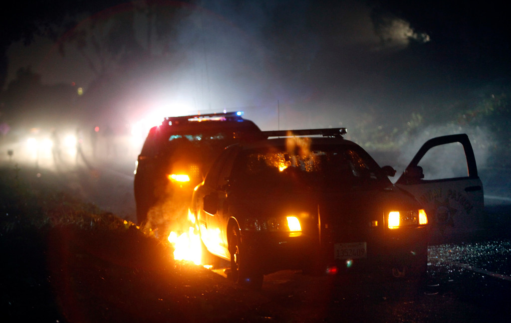 . A CHP squad car is vandalized and set on fire on a Highway 24 offramp in Oakland, Calif., Sunday evening, Dec. 7, 2014, during a second consecutive night of civil disobedience in Berkeley and Oakland over the killings of two unarmed black men by police in Ferguson, Mo., and New York. (Karl Mondon/Bay Area News Group)