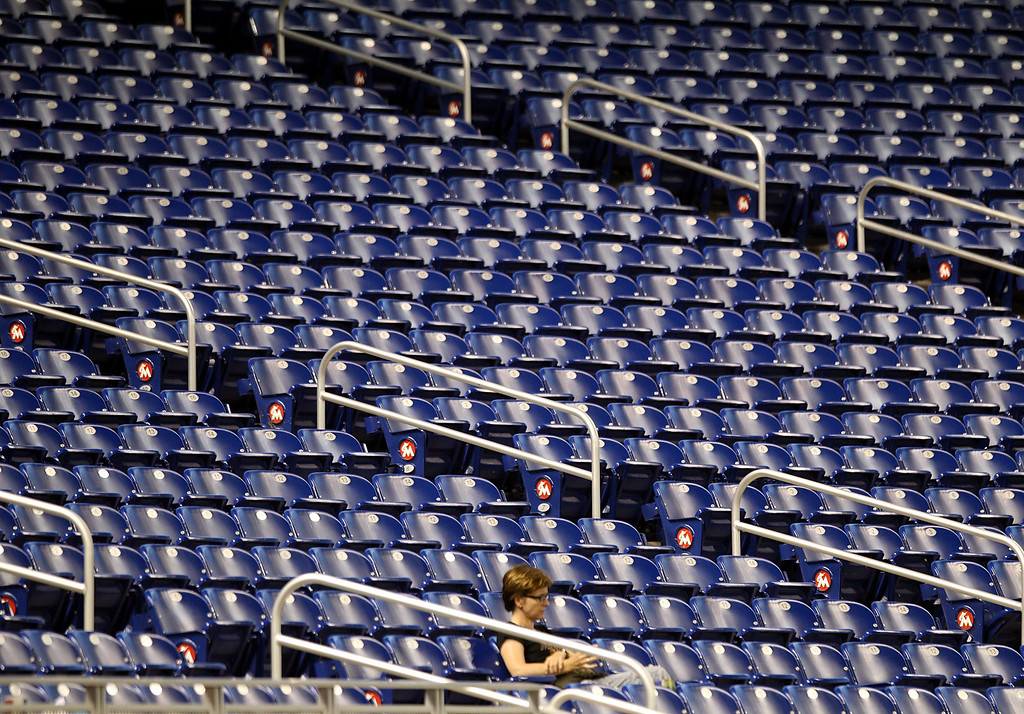 . MIAMI, FL - AUGUST 23:  Fans sit in empty stands as the Miami Marlins play against the Colorado Rockies at Marlins Park on August 23, 2013 in Miami, Florida.  (Photo by Marc Serota/Getty Images)