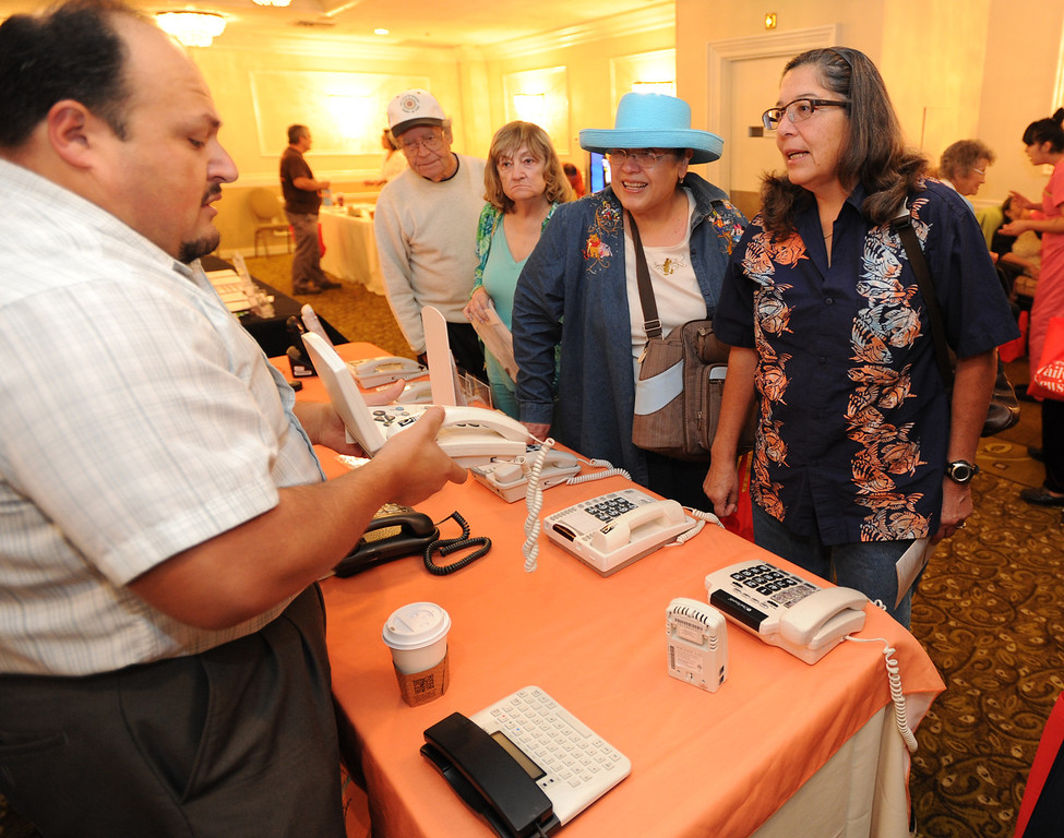 . Fred Navarro, an Outreach Specialist from the California Telephone Access Program talks to Marie Christine Gonzalez and her sister Maria Elena Gomzales. The 4th annual Successful Aging Expo was held Saturday at the Sportsmen�s Lodge Events Center in Studio City, CA. 10/12/2013. photo by (John McCoy/Los Angeles Daily News)