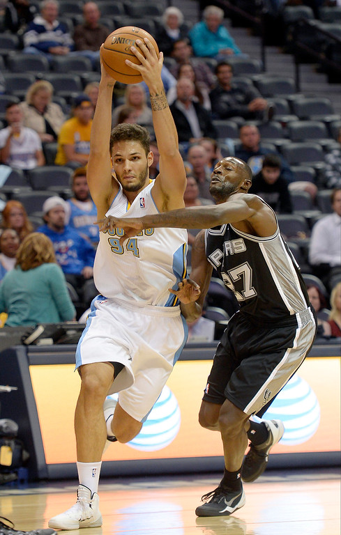 . DENVER, CO - OCTOBER 14: San Antonio Spurs point guard Courtney Fells (27) reaches in on Denver Nuggets shooting guard Evan Fournier (94) as he drives to the basket during the fourth quarter October 14, 2013 at Pepsi Center. (Photo By John Leyba/The Denver Post)
