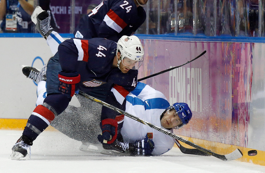 . Finland forward Tuomo Ruutu hits the ice as he challenges USA defenseman Brooks Orpik for the puck during the second period of the men\'s bronze medal ice hockey game at the 2014 Winter Olympics, Saturday, Feb. 22, 2014, in Sochi, Russia. (AP Photo/Mark Humphrey)