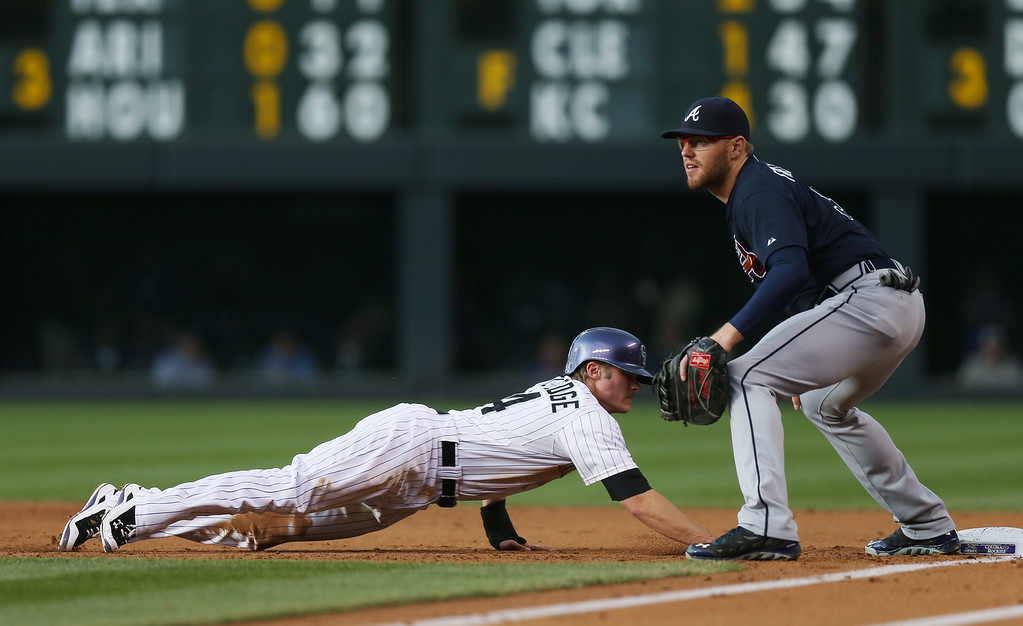 . Colorado Rockies\' Josh Rutledge, left, dives back into first base after taking a lead as Atlanta Braves first baseman Freddie Freeman fields the pickoff throw in the first inning of a baseball game in Denver on Wednesday, June 11, 2014. (AP Photo/David Zalubowski)