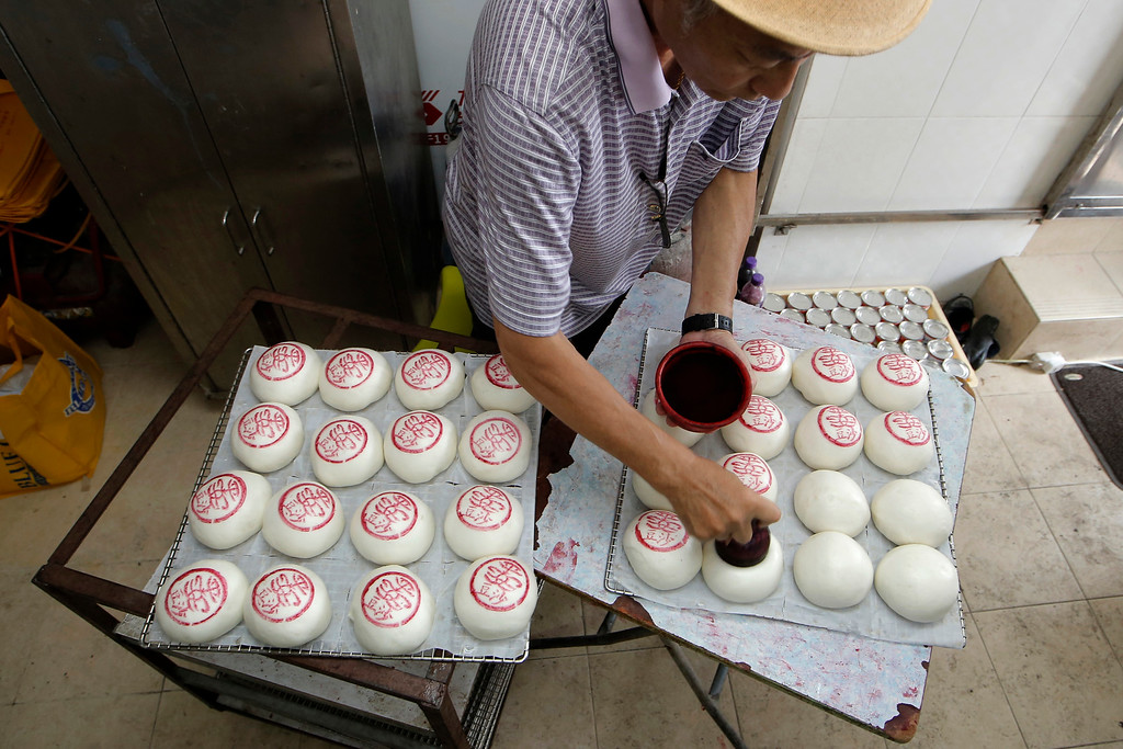 """. A man stamps the sign featuring the Chinese character \""""Peace\"""" on buns for sale on the outlying Cheung Chau island in Hong Kong to celebrate the Bun Festival Tuesday, May 22, 2018. Bun Festival, the Taoist God of the Sea, is worshipped and evil spirits are scared away by loud gongs and drums during the procession. The celebration includes bun scrambling, parades, opera performances, and children dressed in colorful costumes. (AP Photo/Kin Cheung)"""