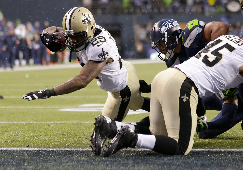 . New Orleans Saints running back Khiry Robinson, left, runs for a 1-yard touchdown during the fourth quarter of an NFC divisional playoff NFL football game against the Seattle Seahawks in Seattle, Saturday, Jan. 11, 2014. (AP Photo/Elaine Thompson)