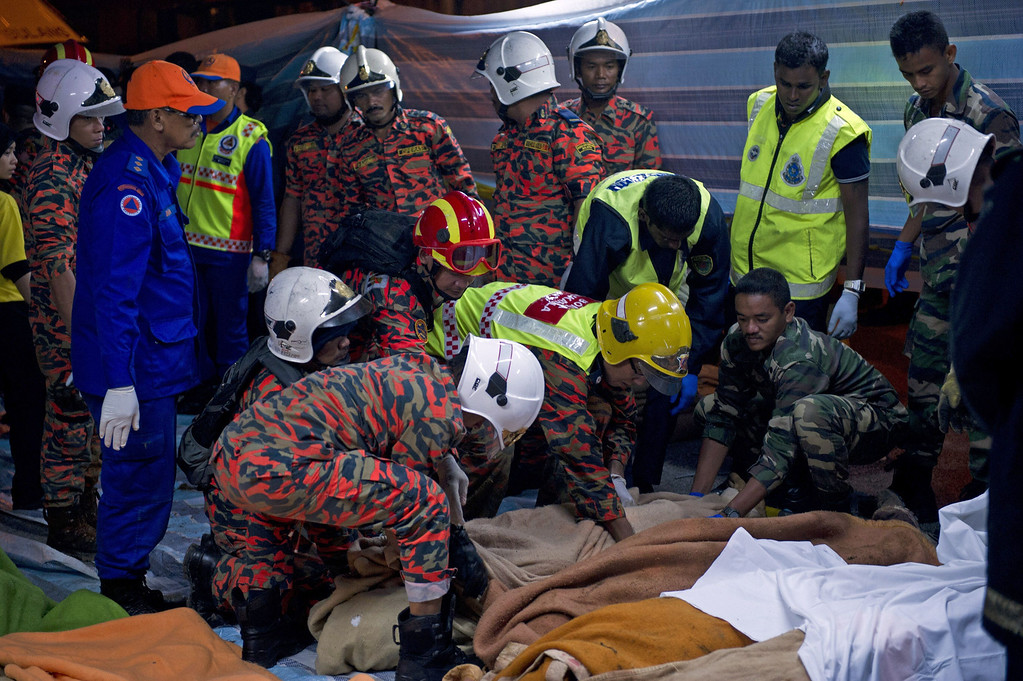 . Malaysian emergency services personnel attend to dead passengers after a bus carrying tourists and local residents fell into a ravine near the Genting Highlands, about an hour\'s drive from Kuala Lumpur on August 21, 2013.         AFP PHOTO / MOHD  RASFAN/AFP/Getty Images