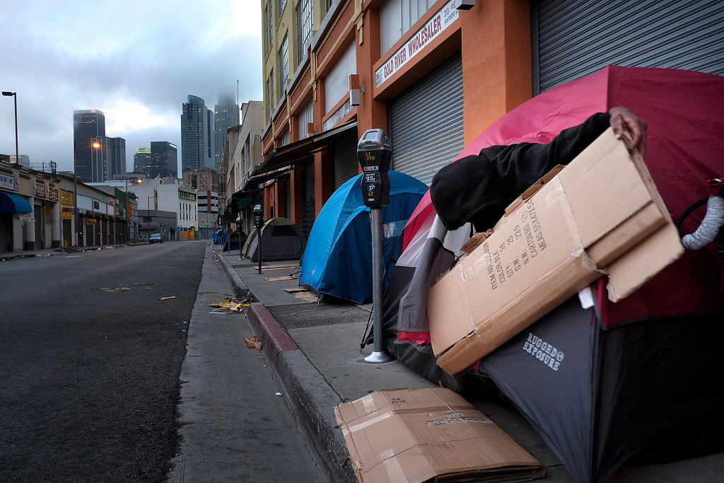 . Torrance Moore, 46, right, prepares cardboard for bedding while setting up a tent on the sidewalk in the Skid Row area of Los Angeles, Friday, March 29, 2013. Homeless people are allowed to pitch their tents between 9 p.m. to 6 a.m. in this particular section. (AP Photo/Jae C. Hong)