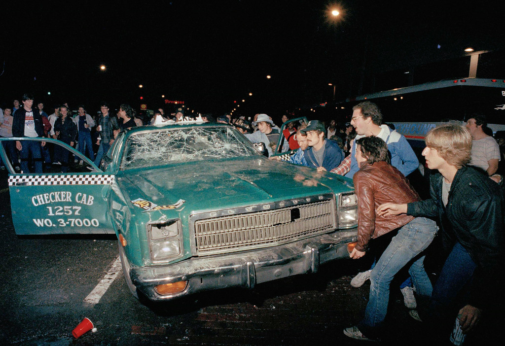 . FILE - In this Oct. 14, 1984 file photo, a crowd attempts to topple a damaged taxi car outside Detroit\'s Tiger Stadium after the Detroit Tigers defeated the San Diego Padres to win the 1984 World Series baseball championship. (AP Photo)