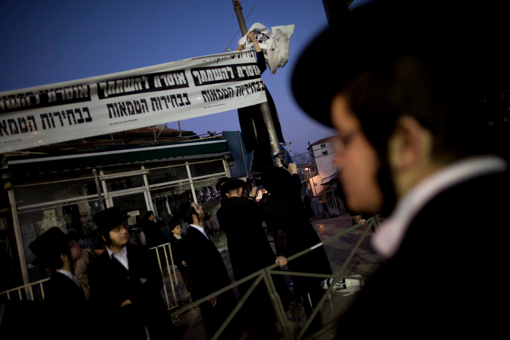 Description of . Ultra Orthodox Jewish man sets up a banner calling not to vote in the upcoming election, the Ultra Orthodox Jewish neighborhood of Mea Shearim in Jerusalem, Sunday, Jan. 20, 2013. General elections in Israel are scheduled for Jan. 22, 2013. (AP Photo/Oded Balilty)