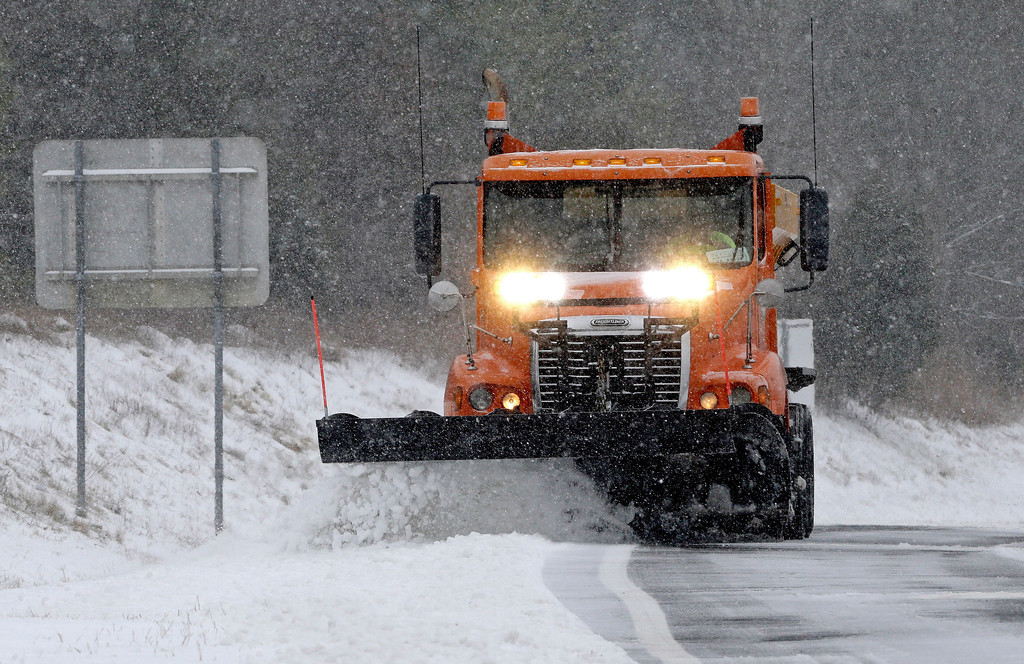 . A truck plows sleet and snow from an onramp along Interstate 40 as snow from a winter storm blankets the area making driving conditions hazardous near Chapel Hill, N.C., Saturday, Jan. 7, 2017. (AP Photo/Gerry Broome)