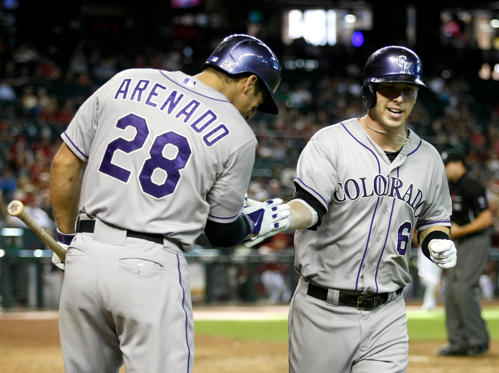 . Colorado Rockies\' Corey Dickerson (6), right, celebrates with teammate Nolan Arenado (28) after hitting a 10th-inning home run against the Arizona Diamondbacks during a baseball game, Sunday, Aug. 10, 2014, in Phoenix. (AP Photo/Rick Scuteri)