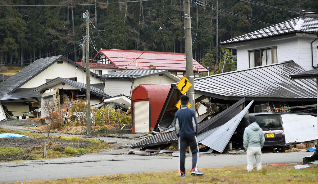 . Residents look at houses collapsed after a strong earthquake in Hakuba, Nagano prefecture, central Japan, Sunday, Nov. 23, 2014. More than 20 people have been hurt after the magnitude-6.8 earthquake shook on Saturday night the mountainous area that hosted the 1998 winter Olympics. (AP Photo/Kyodo News)
