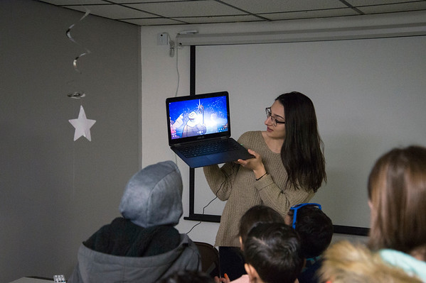 01/06/19 Wesley Bunnell | StaffrrThree Kings Day was celebrated at Neighborhood Services of New Britain at 223 Broad St for families on Monday night. An employee holds up a laptop which played a movie on the story of the Three Kings for children to watch.