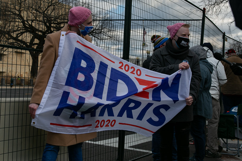 A group of people with Joe Biden gear gather outside of the security perimeter near the U.S. Capitol on inauguration day