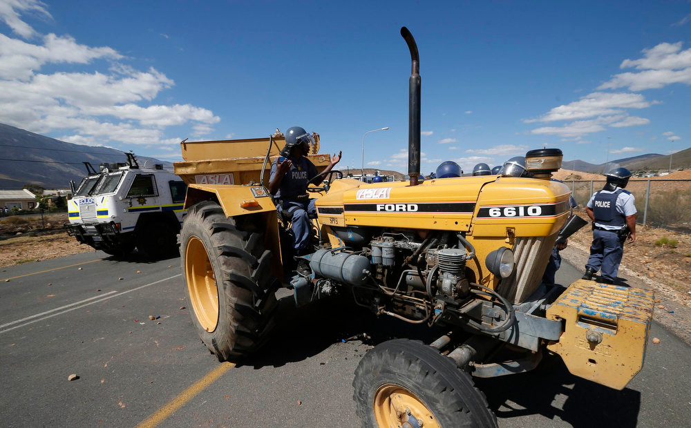 . Police attempt to move machinery damaged during a farm workers strike at De Doorns on the N1 highway linking Cape Town and Johannesburg, January 10, 2013 . Police fired rubber bullets and stun grenades at hundreds of striking farm workers who blocked a highway in the grape-growing Western Cape on Thursday, the first clashes of a year likely to be marked by fractious labour relations.  Hundreds of striking workers seeking higher wages and better working conditions again blocked a major highway running through the town of De Doorns, about 100 kms (60 miles) east of Cape Town, hurling stones at motorists. REUTERS/Mike Hutchings