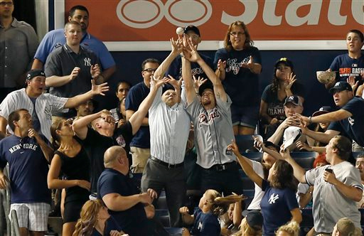 . Two fans reach for a fifth-inning solo home run hit by New York Yankees\' Martin Prado to left field in a baseball game against the Detroit Tigers at Yankee Stadium in New York, Tuesday, Aug. 5, 2014. (AP Photo/Kathy Willens)